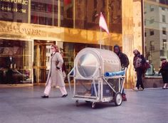 """Krzysztof Wodiczko - """"Homeless Vehicle"""" (1988) The Homeless Vehicle Project disturbed conventional views of homelessness still further by targeting an occupational subculture of single homeless men (those who survive by redeeming empty cans and bottles for five-cent deposits) as potential user-consumers of an ostentatiously designed object."""