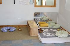 We can make this space: soft rug or quilt (washable) on top of a mat with sheet. Baskets left on the mat create a more homelike feel.
