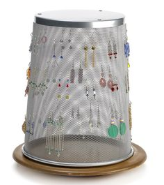 To display many earrings, hang them in the holes of an inverted mesh trash can. Place trash can on a lazy susan.
