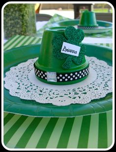 terra cotta leprechaun hats looks simple enough  Green paint Polka dot black and white ribbon Glue Shamrock die cut covered with glitter or not Tag for name