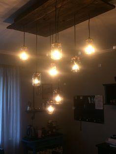 DIY Overhead lighting Ikea Lights, Pallet Wood and copper painted mason jar lids and mason jars.