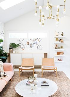 tan leather chairs, pink sofa and brass chandelier // office tour - sarah sherman samuel