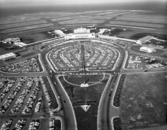 Black and white photographic negative depicting oblique, east-facing aerial view of San Francisco International Airport (SFO), May 27, 1960; roundabout access roadway encircling main parking lot with straight-away view of Terminal Building (now Terminal 2 / T2) west elevation; sunny late-afternoon conditions.