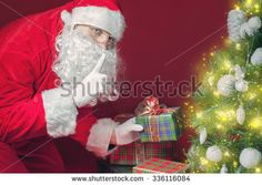 Santa Claus putting gift box or present under Christmas tree at eve night. It's a secret. Surprise! Don't tell the kids! Xmas and New Year holiday! Copy space at red background