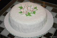 Täytekakku sokerimassapäällysteellä sekä sokerimassasta valmistetuja liljoja.