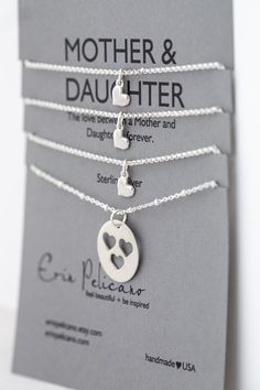 """This set of four necklaces represents the lifelong bond and love between mothers and daughters. The mother's necklace is an 18mm hand-cut sterling heart pendant on an 18″ sterling silver beaded chain. The daughter's necklace is a delicate sterling heart on either a 16″ or 18″ chain. Presented on a Mother & Daughter card that reads, """"The love between a Mother & Daughter is forever."""""""