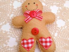 This gingerbread man is made of felt and handstitched using DMC cotton embroidery floss. Decorated with red and white gingham fabric hearts, red and white gingham ribbon and red buttons on the front, and a gingham heart and a metal Gingerbread Crafts, Gingerbread Decorations, Felt Christmas Decorations, Christmas Ornaments To Make, Christmas Sewing, Handmade Christmas, Holiday Crafts, Christmas Crafts, Gingerbread Christmas Decor