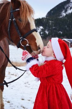 Little girl kissing horse outside in snow..maybe pic of nanny doing same before she sends of her tree with her note tucked inside?  Take good care of it....