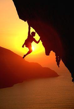 Rock climbing at sunset above the Aegean Sea
