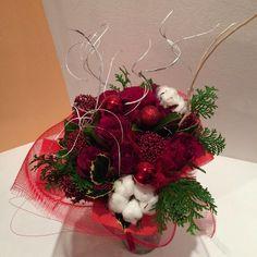 Bouquet natalizio con rose rosse, fiore del cotone, agrifoglio, thuja, schimmia.