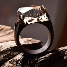 "TINY SNOW FOREST is a ring made from darker wood, light clear jewellery resin and white ""snow"" that glows in the dark."