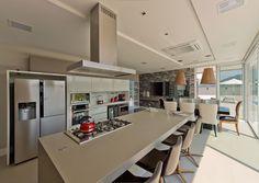 Casa, decoração de casa, casa, com ambientes integrados com tons neutros, como cinza bege, branco e preto. Mesa de jantar, com cadeiras brancas com pendente e luz natural. Na cozinha banquetas estofadas.