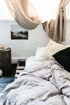 Pallet bed with tree stump table, linen curtains and crochet'd cushions