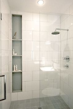 Wall tile & shower niche recessed with extra height and shelving. Light blue matte glass tile finishes the inside of the niche.