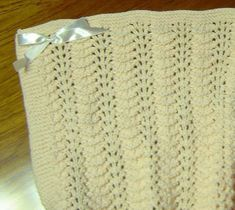 The historic Old Shale lace pattern, also known as Feather & Fan, combined with a simple garter stitch border creates a pretty little blanket for a large baby doll or newborn baby. Or choose one of the larger sizes for a childâs or adult afghan. Extra stitches on the side borders (short rows) ensure that the edge is neat and straight. Design is knit flat in your choice of 6 different sizes.Please note: Original yarn in the pattern has been substituted for yarns shown.