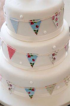 This simple white wedding cake has been decorated with miniature flags tied around each tier to fit in perfectly with a vintage wedding theme.� Ideal for both spring and summer, this super cute wedding cake idea can be re-created from home with ease!