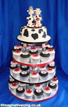 Cupcakes and Cows    Cupcakes in silver cases decorated with black and white smooth icing and alternate red and white flowers.    Available in the colours of your choice  The top cake has a cow print pattern and two comical sugar bride and groom cows on top.