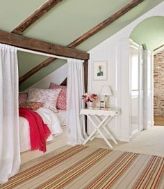 an attic bedroom with curtained bed under the eaves, and green ceiling with beams.