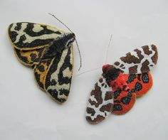 Two Tigers. Wood Tiger moth and Garden Tiger moth by Lisa Toppin. Free machine embroidery, fabric, backed with felt.