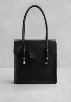 A structured leather tote with a classic shape and gold finish embellishments.