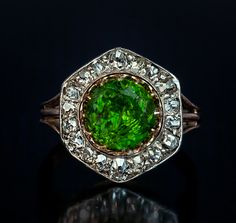 A Rare Almost 3 Carat Russian Demantoid and Diamond Ring, 1908-1917. The silver topped 14K gold ring features a very large vivid grass green 2.84 ct Russian demantoid prong-set in gold, within a hexagonal frame embellished with old cut diamonds.