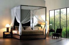 un lit baldaquin en bois et en fer noir avec un voile blanc et fin