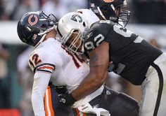 Richard Seymour #92 of the Oakland Raiders hits Caleb Hanie #12 of the Chicago Bears after Hanie threw the ball at O.co Coliseum on November 27, 2011 in Oakland, California.