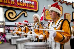 men and women in uniform playing drum at christmas parade. - Men and women in uniform and santa's hat playing drum at Christmas parade.