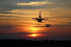 A hex drone and a DJI Phantom fly in the sunset