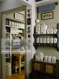 Kitchen with pottery and dishes, wood floor, vintage molds on wall, pantry area, shelving of canisters full of herbs and grains  – Image © Sheltered Images / Masterfile.com: Creative Stock Photos, Vectors and Illustrations for Web, Mobile and Print
