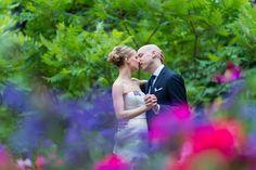 Bride and groom kissing between purple flower in Jardin du Luxembourg gardens in Paris.  Wedding picture taken by wedding photographer in Paris Fran Boloni