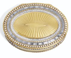AN OVAL GOLD AND GUILLOCHE ENAMEL SNUFF BOX, GERMAN, LATE 18TH CENTURY  oval, the lid, base and sides engine-turned within opaque and translucent blue-grey enamel bands within opalescent bead borders, French prestige marks including J and T crowned