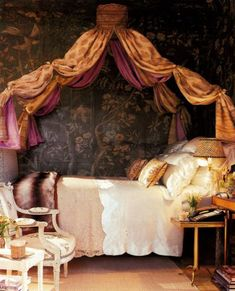 Four poster bed draped in sari fabric with chinoiserie wallpaper white coverlets, such a bohemian old fashioned comfortable nest of a bedroom
