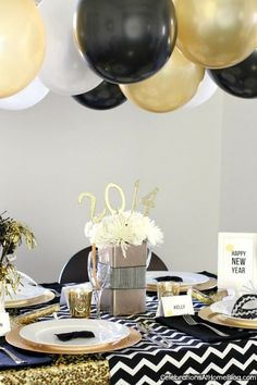 gold black and gold balloons over the reception table so festive and glam new years eve party ideas