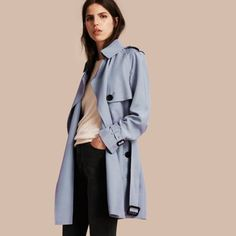 A wrap Burberry trench coat in pale blue, cut long and loose with relaxed raglan sleeves from natural silk with a slightly textured slub finish.