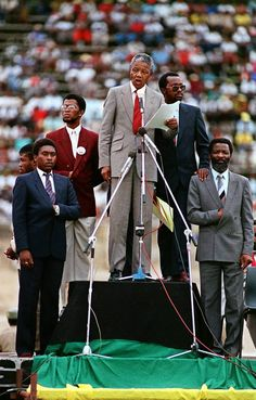 Recently freed anti-apartheid leader and African National Congress (ANC) member Nelson Mandela, center, surrounded by his bodyguards, addresses a mass rally to commemorate the creation of ANC 75 years ago in this conservative South African town.