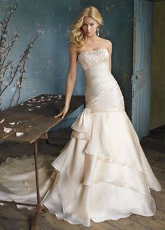 ALVINA VALENTA BRIDAL GOWNS, WEDDING DRESSES: STYLE AV9058       Sherbert silk satin organza bridal gown. Ruched elongated dropped waist bodice with a three-tiered asymmetrical skirt. Beaded trim accents neckline and side bow, sweep train.