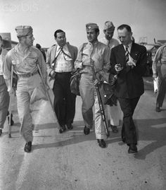 Former athlete Louis Zamperini (right) and Army Capt. Fred Garrett (left) talk to reporters as they arrive at Hamilton Field, Calif., after their release from a 'Jap' prison camp. Capt. Garrett had his left leg amputated at the hip by 'Jap' torturers.