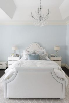 A tray ceiling is accented with a crystal chandelier hanging over a sky blue wall lined with a white arch headboard finished with blue piping dressed in white and gray bedding as well as blue pillows flanked by white 3 drawer nightstands and crystal gourd lamps placed atop a gray Moroccan trellis rug.