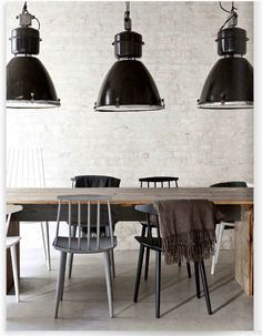 Dig the over-sized dark lamps above the rustic dining table and mismatched chairs