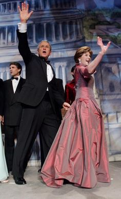 President Bush and first lady Laura Bush wave to supporters as they walk off stage at the Texas State Society's Black Tie and Boots Ball the week's first inaugural gala Wednesday, Jan. 19, 2005 in Washington. Texas' Governor Rick Perry stands to the left of President Bush.