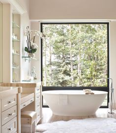 Hildegard's master bath features a freestanding @mti_baths tub with a view of the woods
