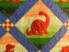 Dinosaur Quilt. I love how the strips of fabric in the background create the scenery. Awesome quilting too!