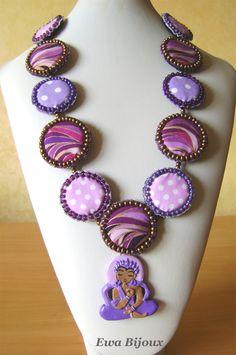 Collier avec pendentif en pâte polymère et avec médaillons en tissu.