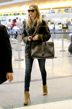 Airport chic: Rosie Huntington-Whiteley covers up her curves in a blanket coat and skinny jeans at LAX airport on Thursday night