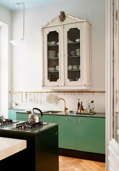 simplicity...grass green cabinetry with that brass rail and a provincial white cabinet overhead...