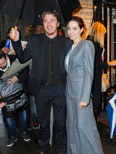 TAKE COVER | Such a gentleman! Actor Garrett Hedlund shields Angelina Jolie from the New York City rain on Tuesday at a screening of Unbroken.