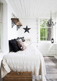 White Nordic summer house bedroom with a little bit of whimsy in the black accents.
