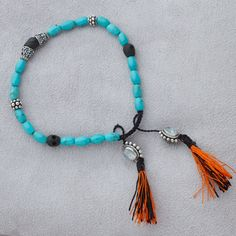 Gangba Bracelet - Hand carved wood mini-skull center anchored by beads of silver, turquoise, and moonstones with black and orange hand tied tassels