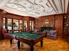 Stunning library/billiards room fully customized in cherry wood, glass-front cabinets for collectibles, library shelves with ladder access, and fireplace; hand sculptured relief ceiling and walnut floors.  #billiards #pool table #library #plaster
